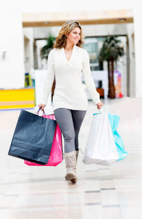 Woman walking at the shopping center and holding bags  photo