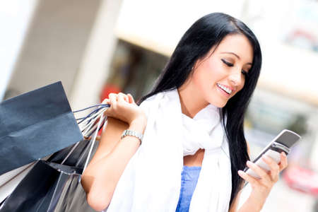 mobile shopping: Shopping woman sending a text message on her cell phone