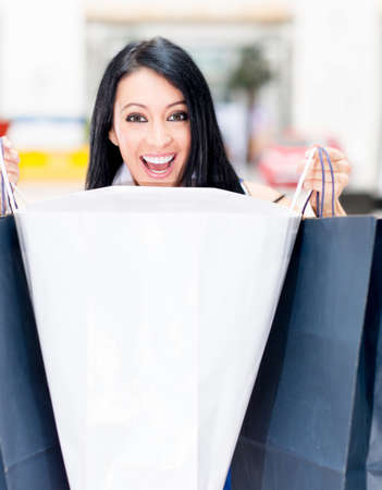 Surprised female shopper opening shopping bags and smiling  photo