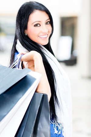 chicas comprando: Hermosa mujer con bolsas de compras en el centro comercial Foto de archivo