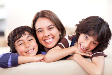 mothers group: Happy mother with her two sons smiling at home Stock Photo