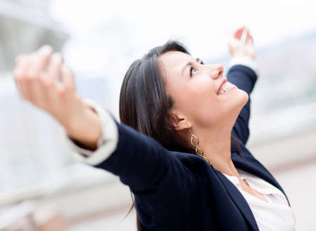 Successful business woman celebrating with arms up photo