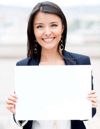 business: Happy businesswoman holding a white banner and smiling
