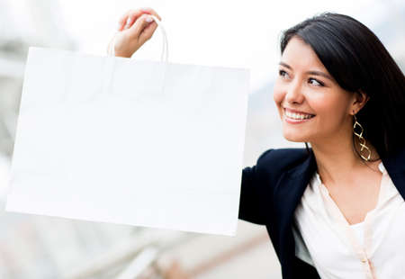 Latin woman holding a shopping bag and smiling  Stock Photo - 13977646