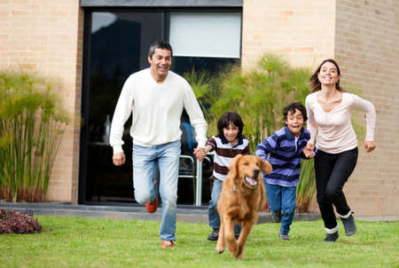 Happy family running after a dog outdoors  photo