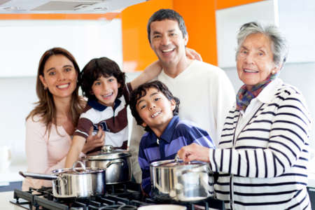 latin family: Happy Latin family cooking together at home  Stock Photo