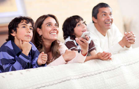 Happy family watching tv together and lying in bed  photo
