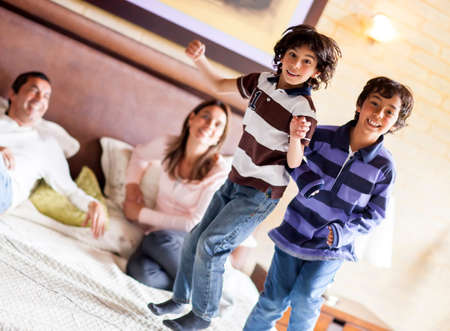 naughty child: Happy kids jumping on the parents bed and having fun  Stock Photo