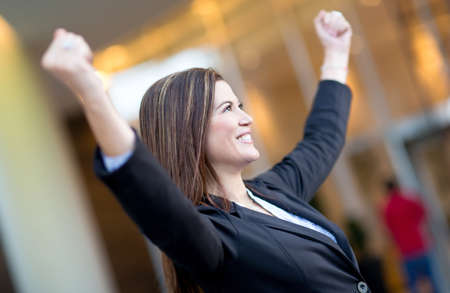 business woman: Successful business woman with arms up celebrating