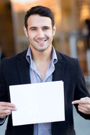 Businessman holding a white poster and smiling  photo