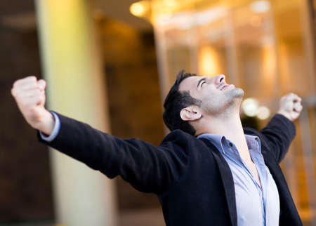 victory: Successful businessman with arms up celebrating his victory