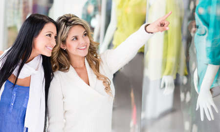 Beautiful shopping girls pointing a at a window  photo