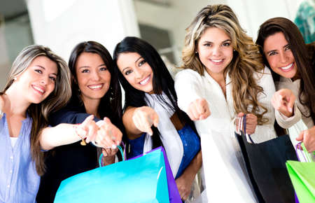 purchases: Group of happy shopping women pointing at the camera