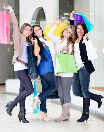 Happy shopping women with arms up at the mall photo