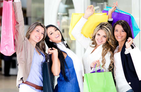 Group of beautiful shopping women with arms up holding bags  photo
