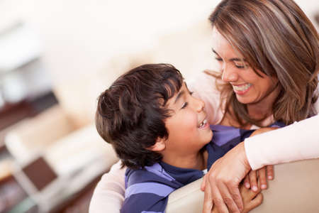 Happy mother with her son smiling at home photo