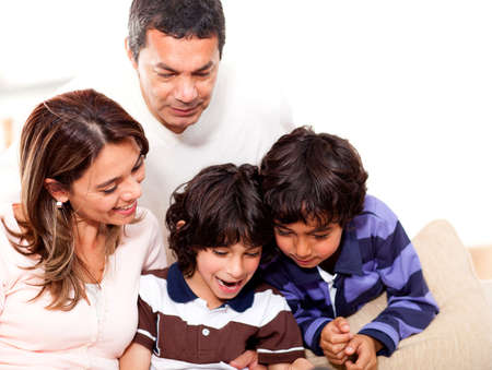 Happy family at home reading a book together  Stock Photo - 14024274