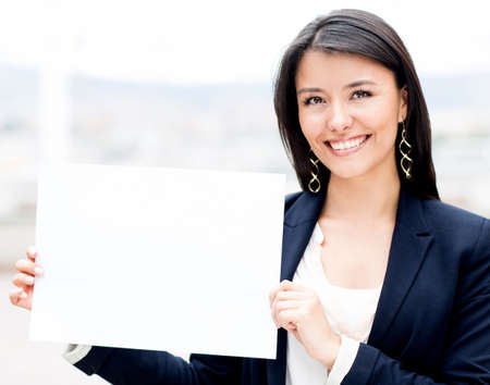 Businesswoman holding a white poster and smiling photo