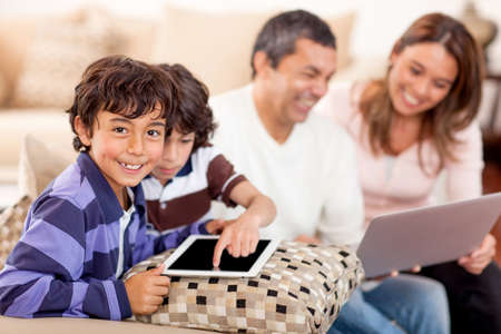 connecting: Family loving technology with a laptop and tablet computer