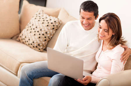 Couple at home going online on a laptop computer  photo