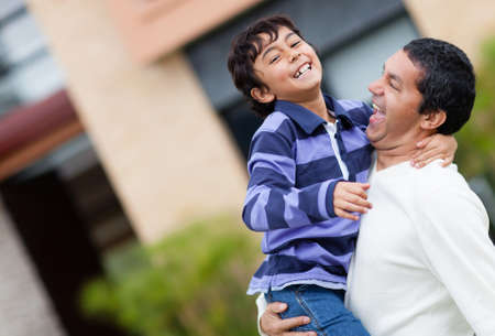Father and son playing outdoors and looking very happy  photo