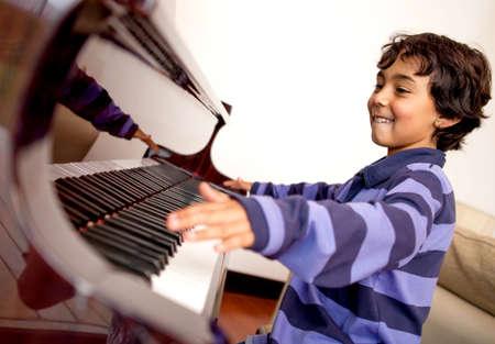 fortepian: ChÅ'opak wyglÄ…daÅ' na bardzo podekscytowani naukÄ™ gry na fortepianie Zdjęcie Seryjne