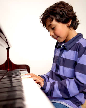 Cute boy playing the piano at home  photo