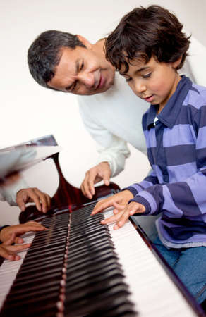 lessons: Boy taking piano lessons at home with a tutor