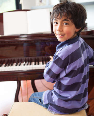 Happy boy playing the piano at home  photo