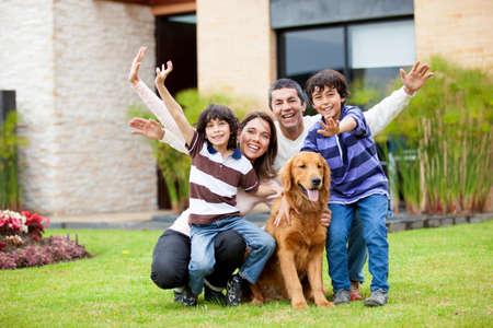 hispanic boy: Familia feliz con un perro fuera de su casa