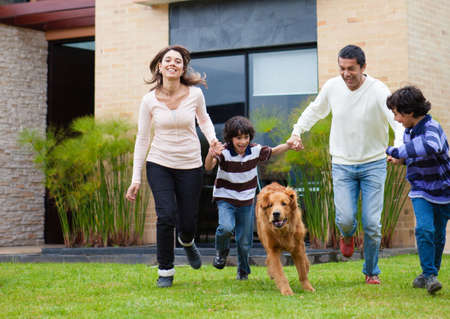 latinos: Happy family chasing a dog and having fun
