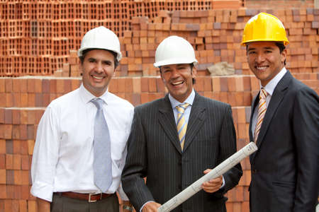 protection plan: Architects at a construction site holding the blueprints