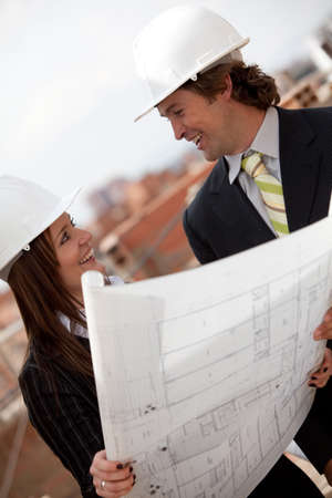 Architects at a construction site looking at blueprints  photo
