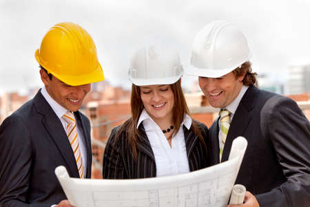 Group of architects at a construction site looking at the blueprints  photo