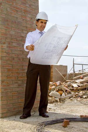 Male engineer at a construction site looking at blueprints   photo
