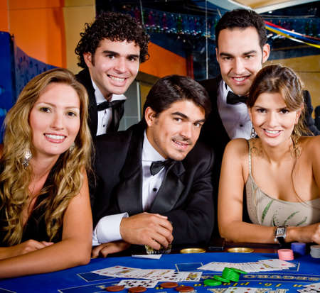 roulette player: Group of people smiling playing roulette at the casino
