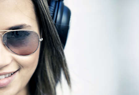 hearing protection: woman wearing headphones and listening to music - urban style