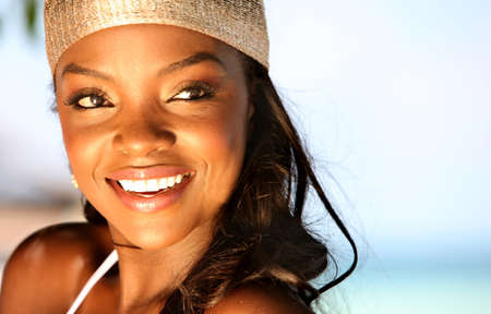 the descendant: Beautiful black woman in bikini at the beach smiling
