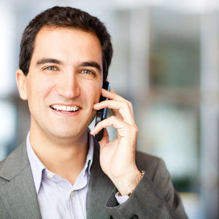 Businessman talking on his cell phone at the office  photo