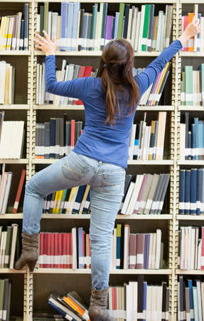 Woman looking for a book at the library  Stock Photo - 14107703