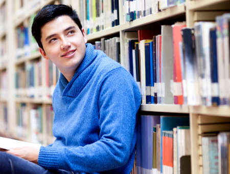 Young man at the library holding a book  photo