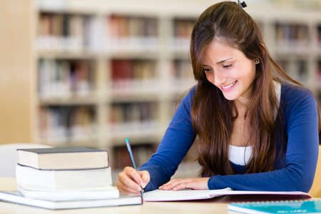 adult learning: Ragazza in biblioteca a studiare con libri
