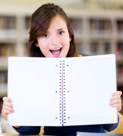 Student at the library holding with an open book  photo