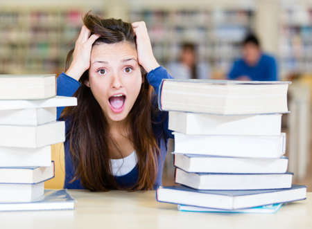 Frustrated female student with a pile of books at the library  Stock Photo - 14131027