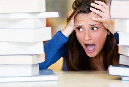 frustrated student: Worried female student with a lot of work to do  Stock Photo