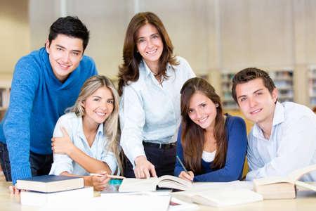 estudiantes universitarios: Grupo de estudiantes universitarios en la biblioteca y sonriente