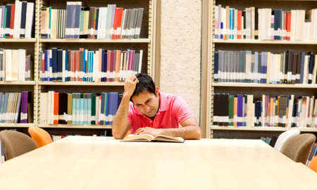 frustrated student: Frustrated male student reading a book at the library
