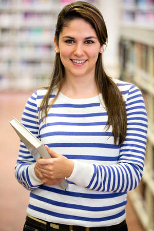 Beautiful woman at the library holding a book  photo