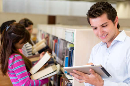 look for: Man with an e-book reader while his friends look for books at the library