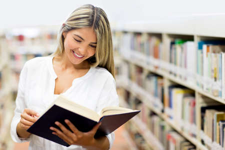 Beautiful woman at the library reading a book  Stock Photo - 14131048